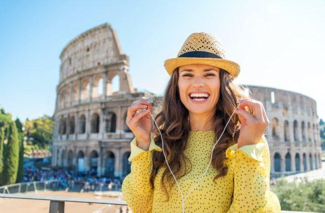 A happy, smiling woman stands near the Colosseum, is removing her earbuds.